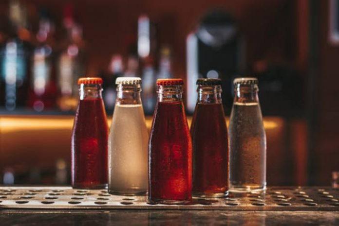 Em cima de balcão de madeira, 5 garrafas pequenas de bebidas, em tons escuros e transparentes.
