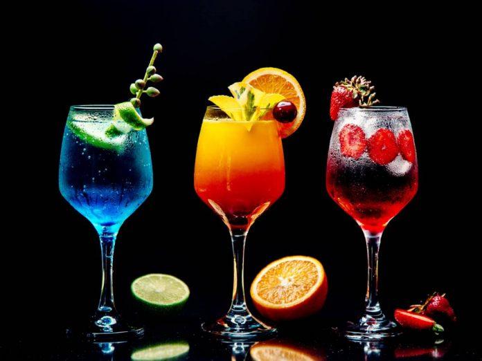 3 taças, sendo uma taça com bebida azul à esquerda, uma taça com bebida laranja ao centro, e uma taça com bebida vermelha à direita, em fundo totalmente preto, realçando as cores de cada líquido