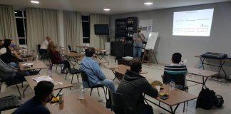 Pessoas sentadas em carteiras em sala de aula, com distanciamento social entre elas, enquanto uma delas faz apresentação na frente, à direita da imagem