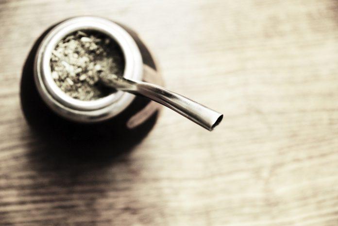 Em mesa de madeira clara, recipiente metálico que guarda chimarrão, com erva-mate na superfície, e canudo metálico