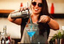 Mulher branca de óculos escuros com coqueteleira na mão despeja bebida azul por meio de coador de coquetelaria em taça transparente, destacando o azul da bebida, em cima de balcão de bar com garrafas e itens de preparo de drinks ao redor