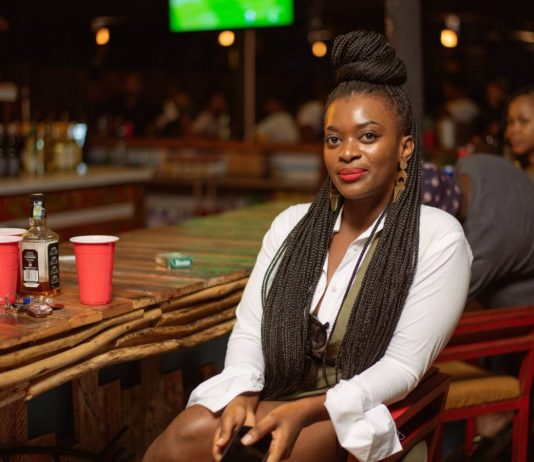 Mulher negra com tranças veste camisa branca e posa para foto sentada em banco em frente a balcão de bar, com outras pessoas que aparecem desfocadas ao fundo da imagem