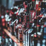 Garrafas de bebidas em tons escuros e marros em cima de prateleira, em ambiente de bar