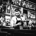 Foto em preto e branco de homem branco com uniforme de bartender enchendo dosador enquanto prepara drink em cima de balcão de bar, com prateleiras e garrafas de bebidas ao fundo.