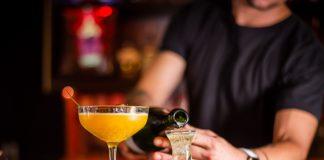 Homem branco veste camiseta manga curta preta enquanto enche pequena taça com bebida, ao lado de taça maior com bebida laranja, em cima de balcão de bar