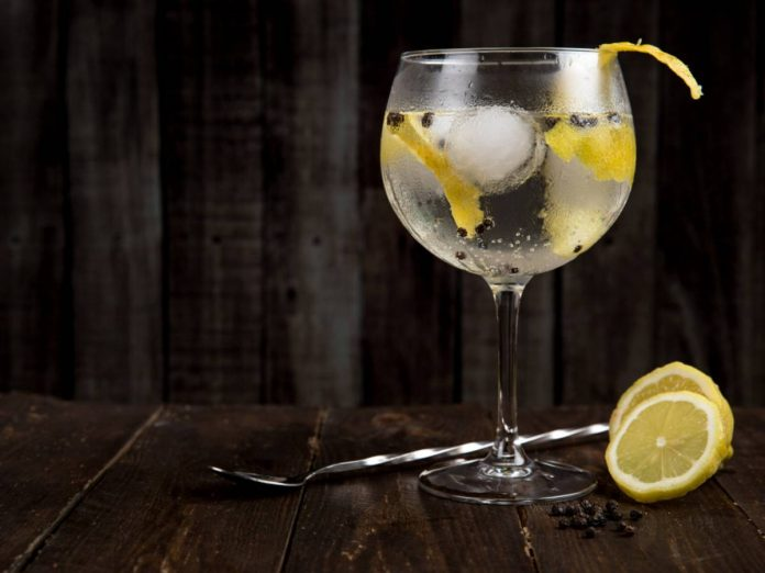 Em fundo escuto, taça transparente de bebida é destacada, com líquido transparente, rodelas de limão e gelo em seu interior, em cima de superfície escura com rodelas de limão cortadas e colher de coquetelaria prateada apoiada