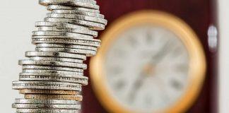Em primeiro plano, pilha de moedas de cor prata, com relógio de borda dourada e painel de números e ponteiros desfocado ao fundo, à direita da imagem
