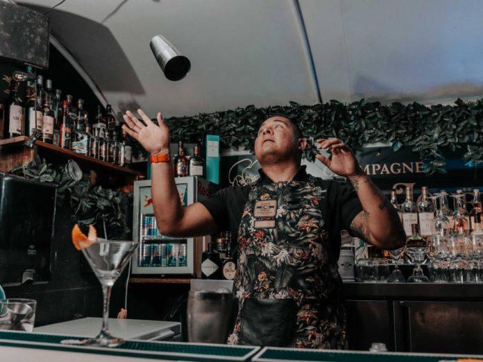 Barman joga coqueteleira prateada para cima durante preparo de coquetel em ambiente de bar, com prateleiras de bebidas ao fundo e taça transparente em cima do balcão à frente do profissional, que veste camisa preta e avental escuro
