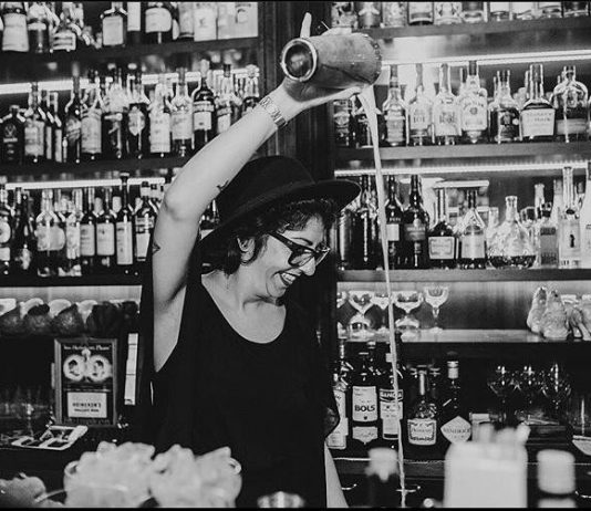 Em foto em preto e branco, Chula Barmaid sorri enquanto despeja líquido de coqueteleira em copo enquanto está atrás de balcão de bar, com prateleiras de garrafas de bebidas ao fundo
