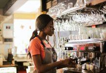 Barista negra com camiseta laranja e avental cinza trabalha em extração de café em máquina atrás de balcão de estabelecimento, com copos suspensos em cima da máquina, com ambiente de bar e janelas ao fundo