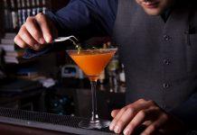 Homem branco que veste roupas escuras de bartender termina de preparar drink de cor laranja em taça transparente, em cima de balcão de bar, com livros e bebidas ao fundo