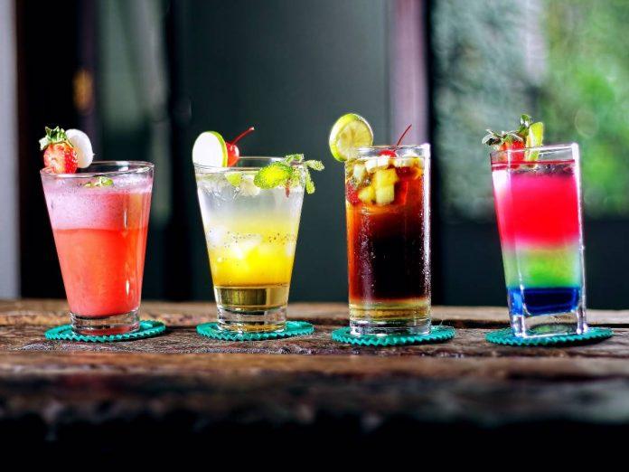 Em cima de balcão de madeira, quatro copos de coquetéis coloridos, o primeiro de tom goiaba, o segundo de tom amarelado, o terceiro de tom marrom e o quarto com camadas vermelha, verde e azul,